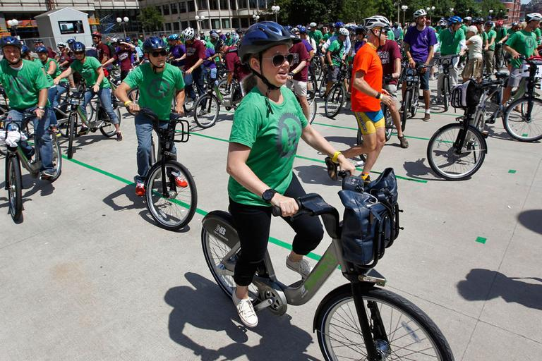 Boston's Tish Simmons, front, and other cyclists depart Boston's City Hall Plaza Thursday as part of a launch of the state's first bike-share program — Hubway. (AP)