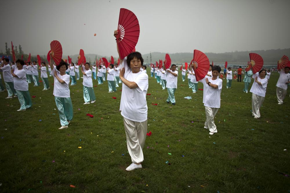 Women perform a fan dance during a ceremony of a government campaign to promote physical exercises at Beijing's Olympic Forest Park in China. (AP)