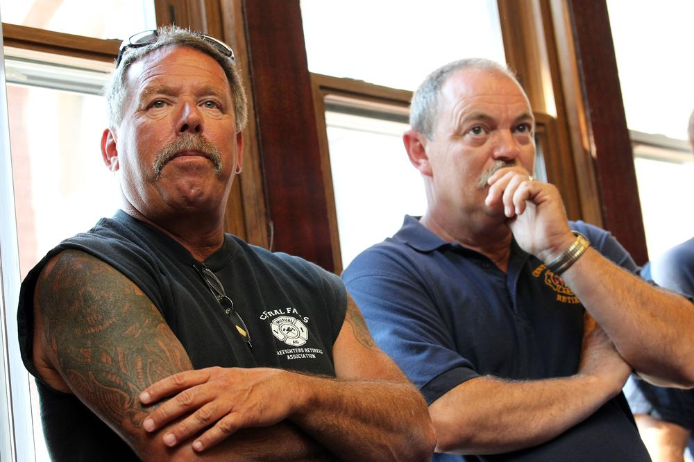 Retired Central Fall, R.I., firefighters Rick McDermott, left, and Paul St. George, right, react as it is announced that the city will file for Chapter 9 bankruptcy protection. (AP)