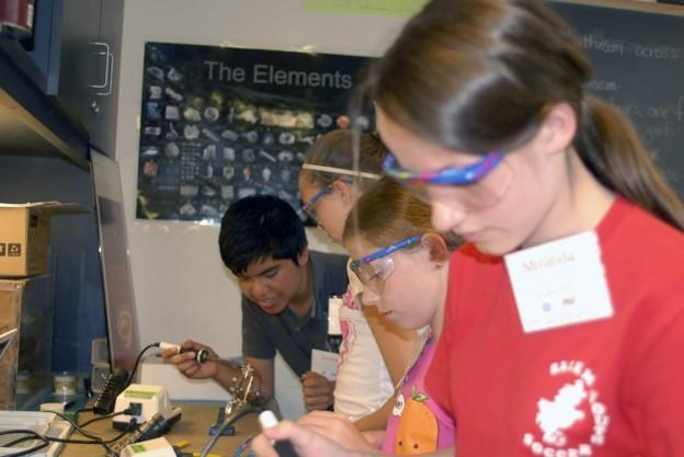 MIT student Victor Morales, far left, teaches students how to solder electronic connections. (Courtesy MIT Edgerton Center)
