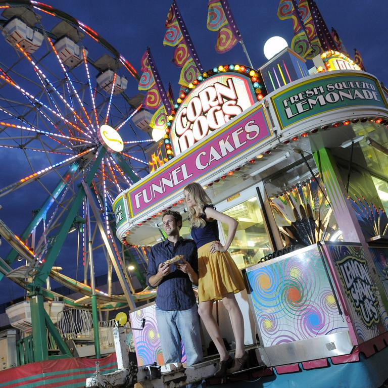 Luke Gunn, left, and Jacqueline Allee, right, both of Pueblo, have their picture taken on the midway for an engagement photo session at the first Denver County Fair in Denver. (AP)