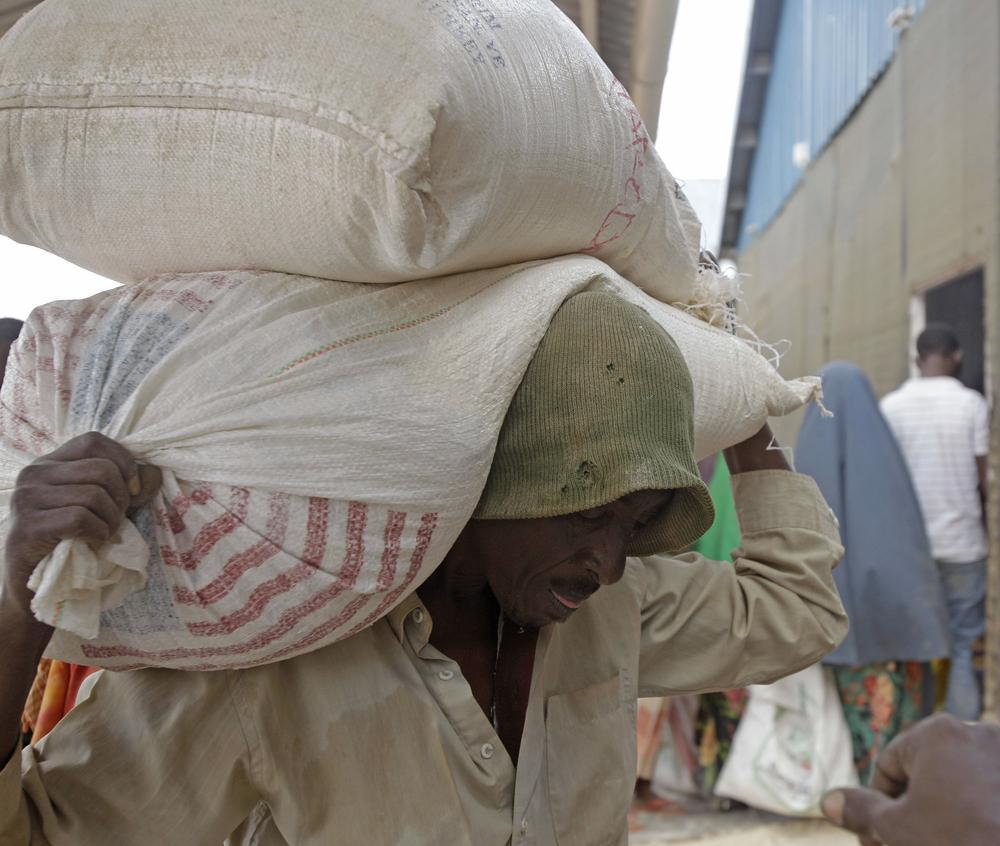 A refugee carries food aid on his back at a food distribution center run by the World Food Programme in the town of Dadaab, Kenya. (AP)