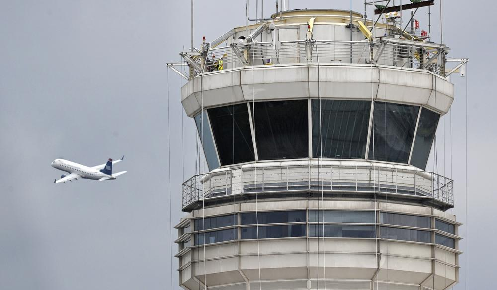 A passenger jet flies past the FAA control tower at Washington's Ronald Reagan National Airport. (AP)