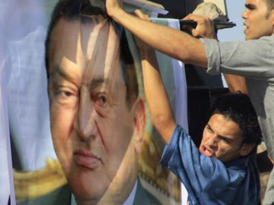 An Egyptian pro-Mubarak protester erects a poster of the ousted president on Wednesday outside the police academy in Cairo. (AP)