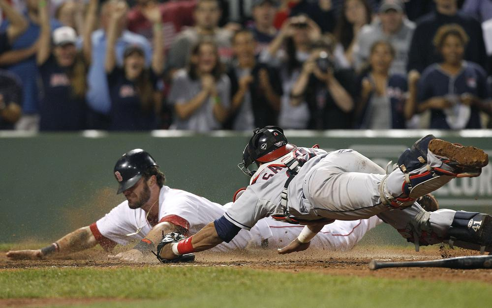 Boston Red Sox's Jarrod Saltalamacchia dives for home plate to score the winning run as Cleveland Indians catcher Carlos Santana tries to tag him in the ninth inning Tuesday. (AP)