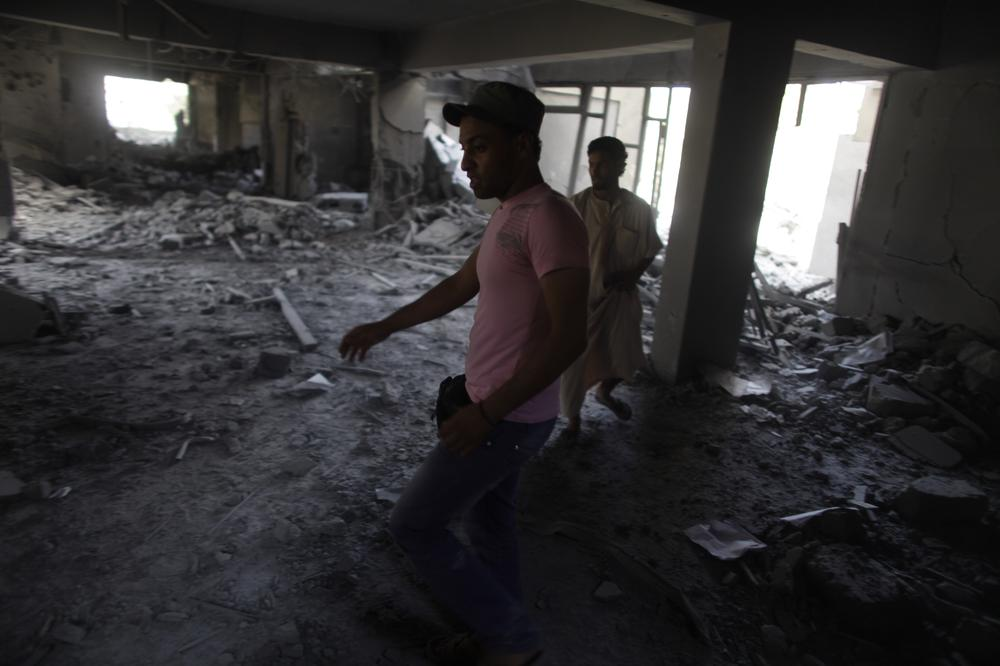 In this photo taken on a government-organized tour men stand inside the rubble of the law school building in Zliten, Libya, Thursday. In recent weeks Libya's rebels have been slowly advancing on Zliten aided by NATO airstrikes. (AP)