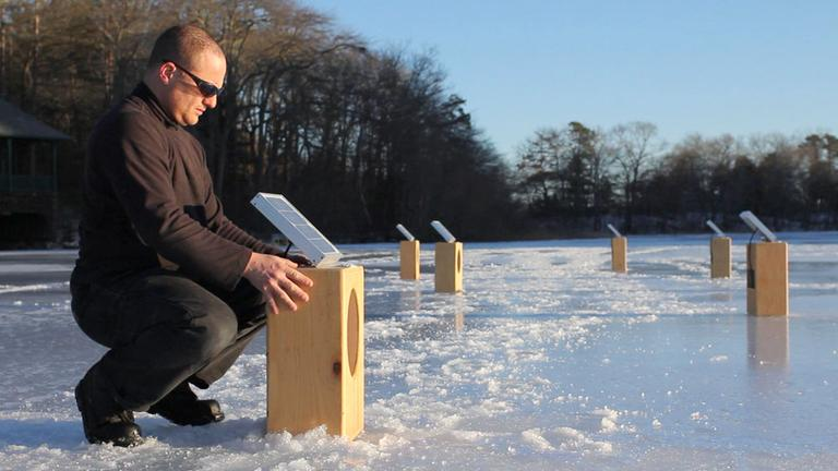 "Artist Craig Colorusso arranges his ""Sun Boxes"" on a frozen pond in Plymouth in February. (Courtesy Kevin Belli)"