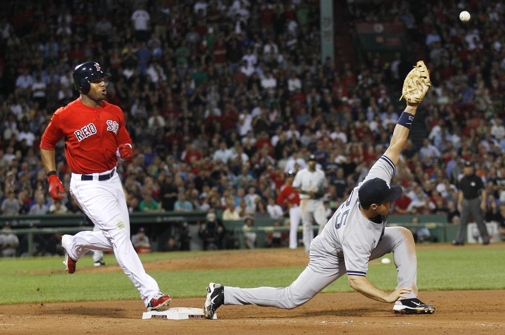 Red Sox outfielder Carl Crawford beats the throw as Yankees first baseman Mark Teixeira stretches for the ball on a single in the ninth inning at Fenway Park, Friday. (AP)