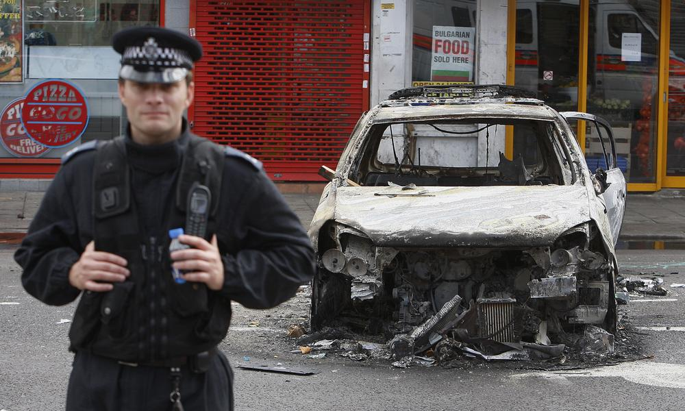 A police officer stands guard in front of a burned police car in Tottenham, north London. (AP)