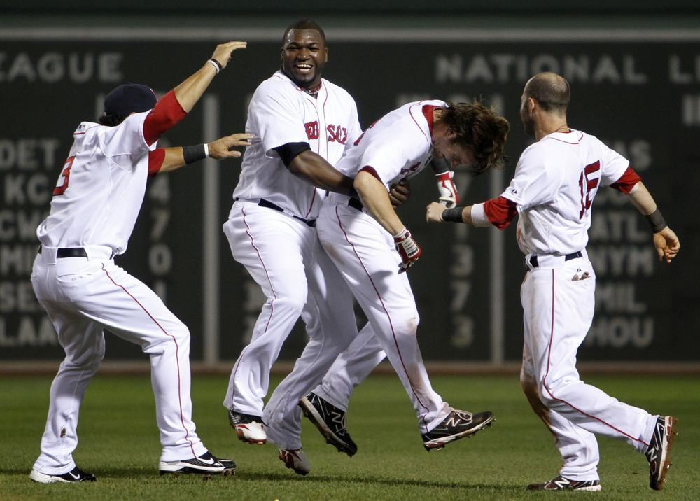 Boston's David Ortiz, second from left, lifts Josh Reddick, second from right, as Mike Aviles, left, and Dustin Pedroia, right, come in to celebrate after Reddick's RBI single gave the Red Sox the walk-off, 3-2 win against New York in the tenth inning of the game in Boston on Sunday. (AP)