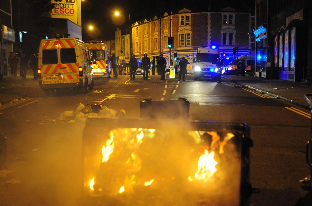 A trash bin burns as police officers patrol the streets in Bristol, England. (AP)