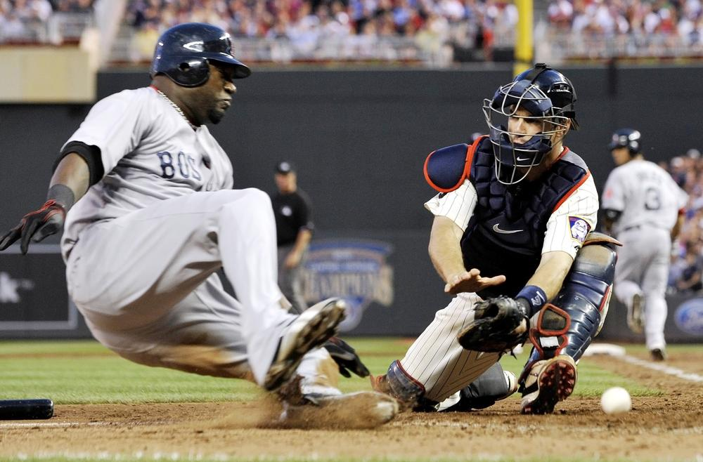 Boston's David Ortiz, left, comes in to score from third as Minnesota catcher Joe Mauer can't handle the throw on a fielders choice hit into by Mike Aviles in the eighth inning of the game on Monday in Minneapolis. (AP)