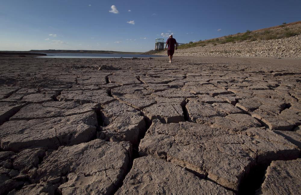 Eddie Ray Roberts, superintendent of the city's waste and water department, walks on the dried bed of Lake E.V. Spence in Robert Lee, Texas. (AP)