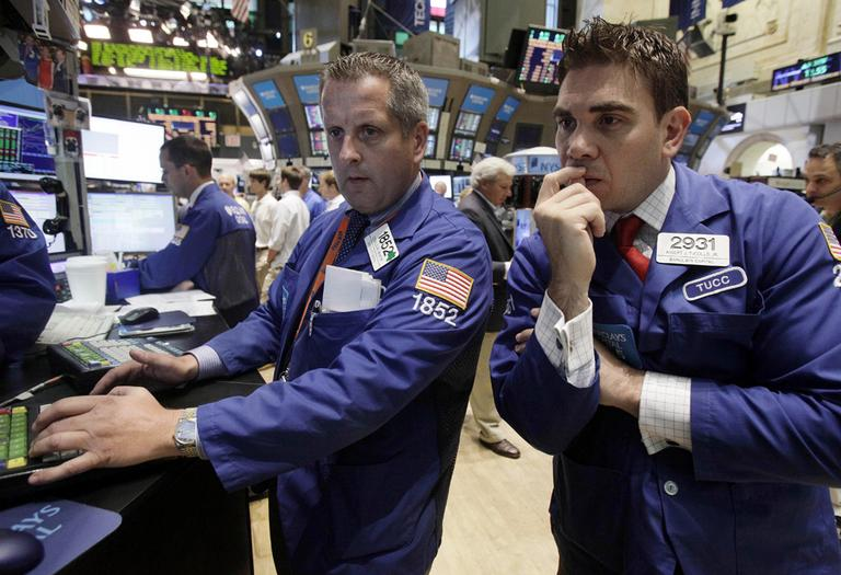 Specialists Donald Vaneck, center, and Robert Tuccillo work on the floor of the New York Stock Exchange Tuesday. (AP)