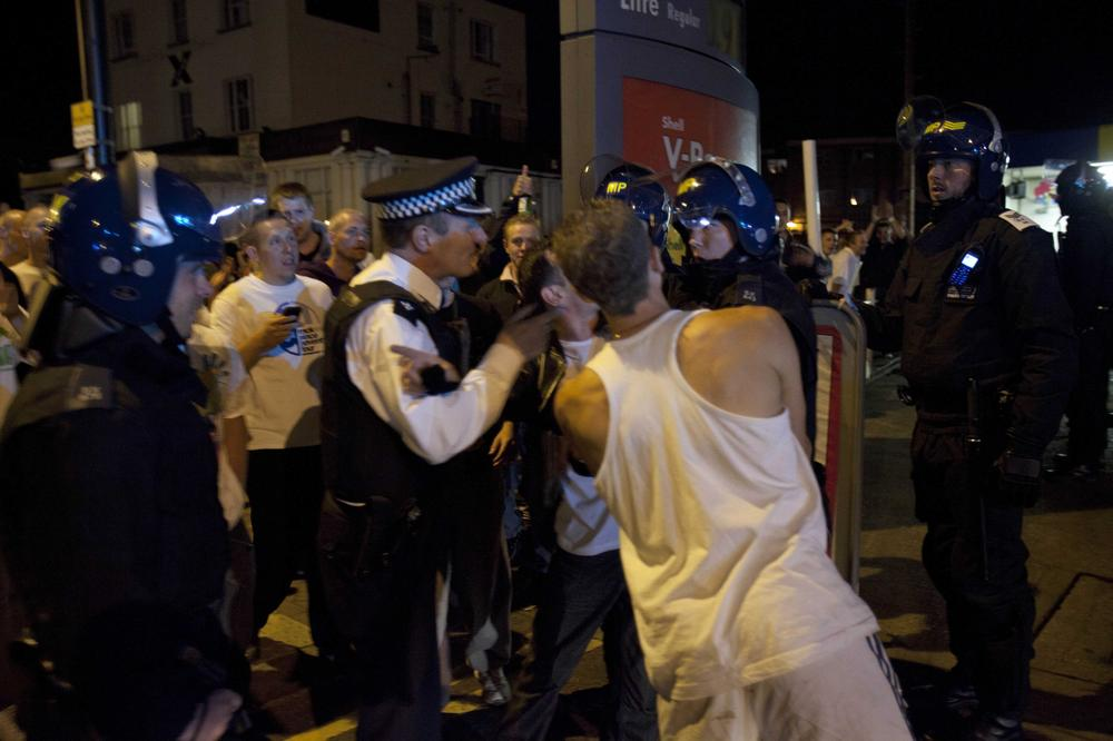 Police officers scuffle with men as members of the community march to reclaim their streets on Tuesday in Enfield, North London. (AP)
