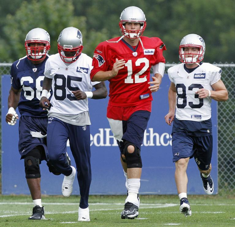 Patriots quarterback Tom Brady (12) runs a drill with defensive end Aaron Carter, left, wide receiver Chad Ochocinco (85) and wide receiver Wes Welker (83) during training camp in Foxborough, Tuesday. (AP)
