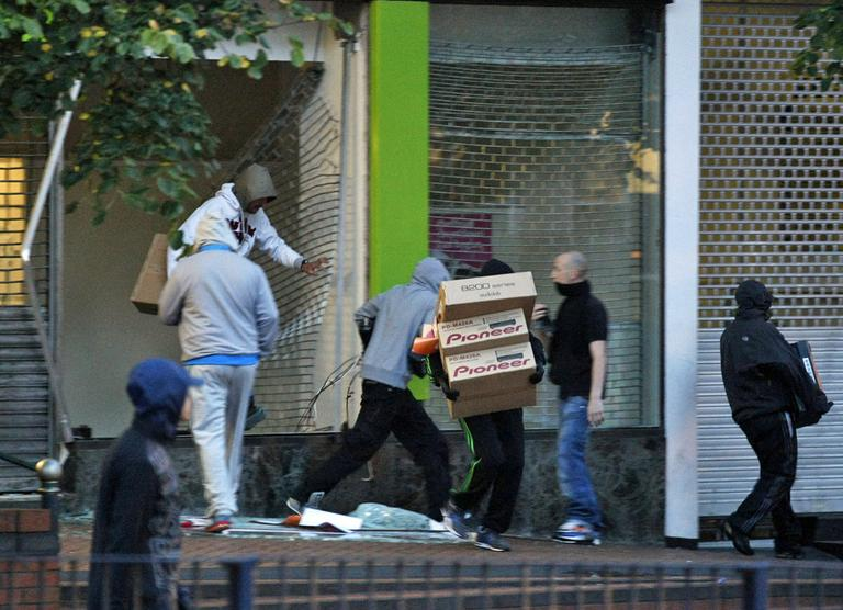 Looters take electrical goods after breaking into a store during the second night of civil disturbances in central Birmingham, England, Tuesday, Aug. 9, 2011. (AP)