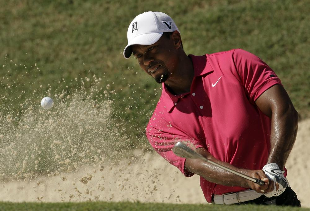 Tiger Woods hits out of a bunker during the first round of the PGA Championship golf tournament Thursday, in Johns Creek, Ga. (AP)