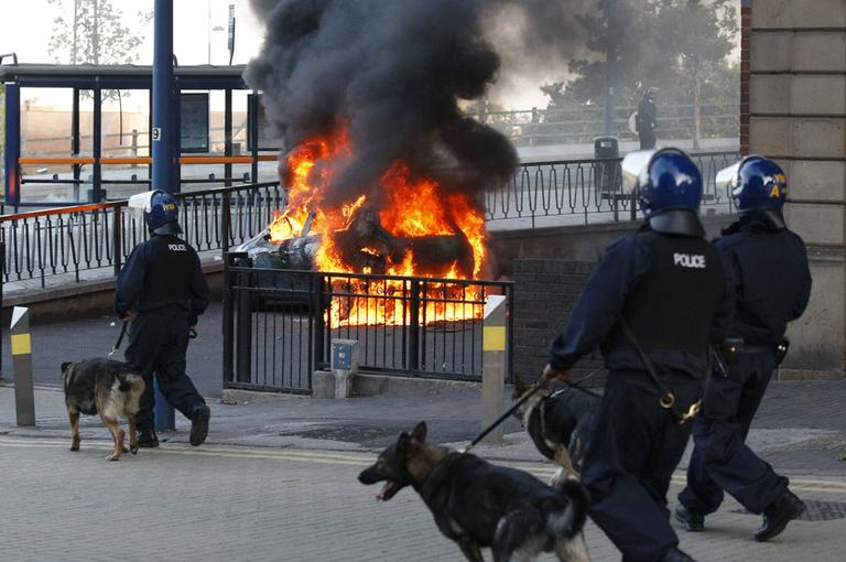 A Police dog and its handler walk past a burning car during the second night of civil disturbances in central Birmingham, England, Tuesday, Aug. 9, 2011. (AP)