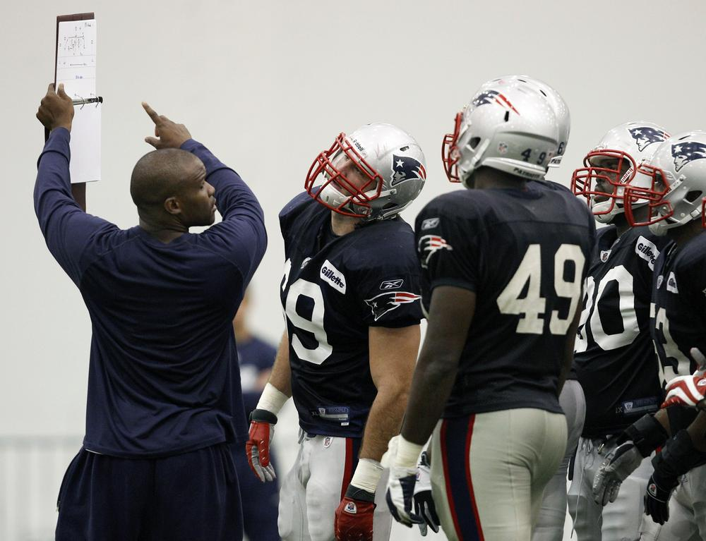 New England Patriots defensive assistant coach Brian Flores goes over a play during NFL football training camp in Foxborough, Mass. on Monday. (AP)