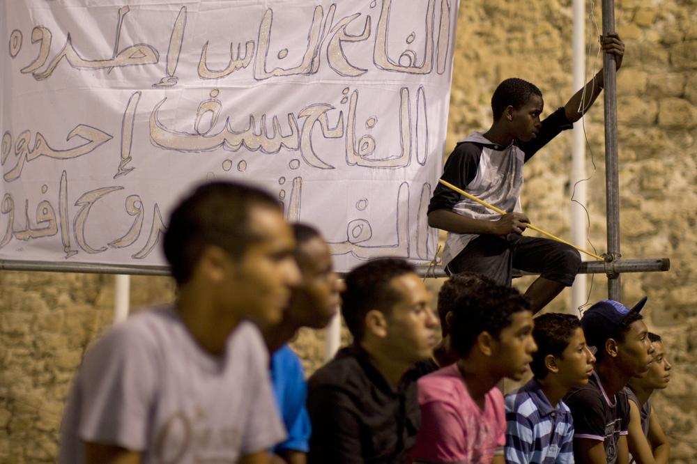 In this photo taken on a government-organized tour, young men watch the activity as music supporting the government of Libya's Moammar Gadhafi plays at the main Green Square in Tripoli, Libya. (AP)
