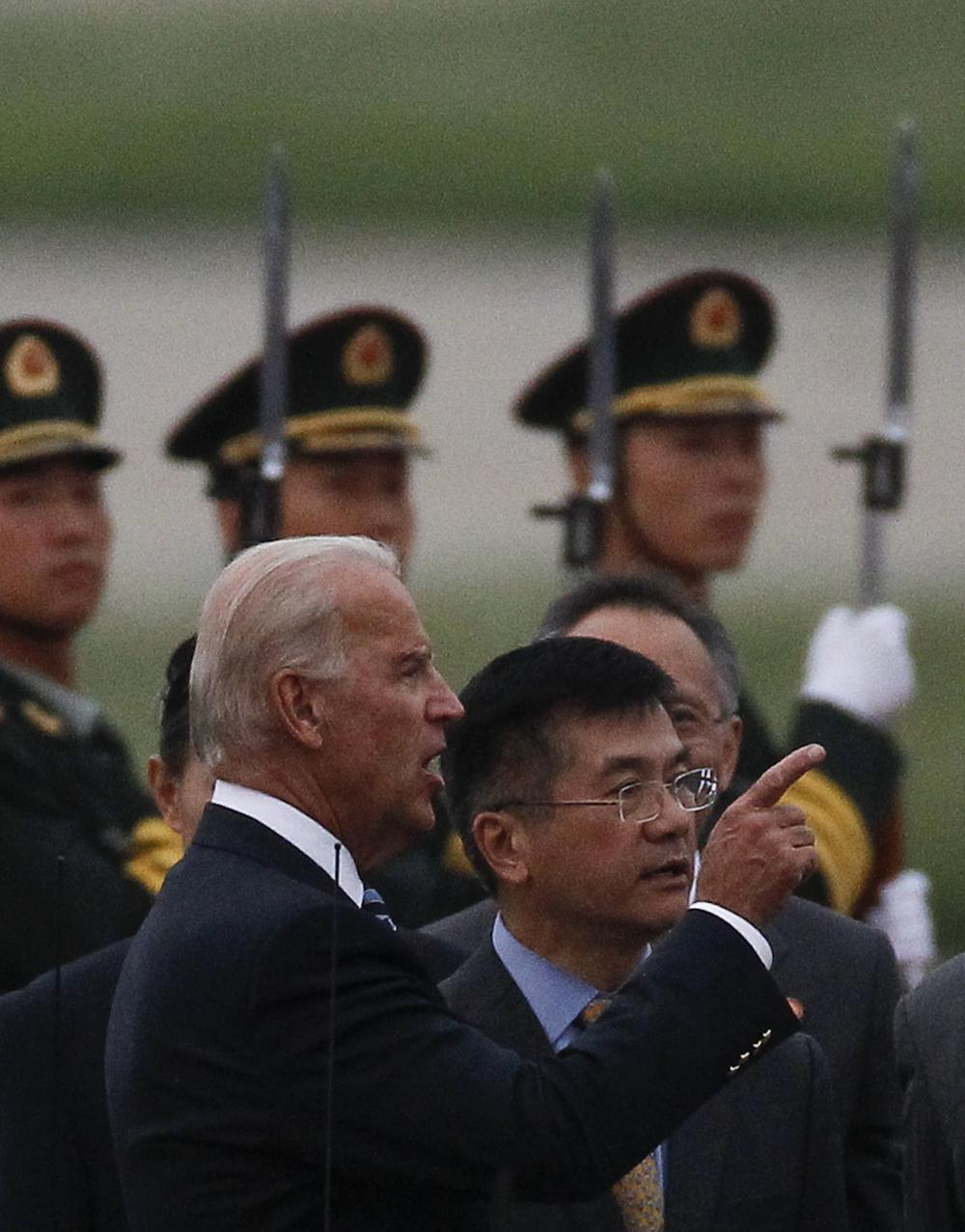 U.S. Vice President Joseph Biden, left, talks with U.S. Ambassador to China Gary Locke, right, after Biden's arrival in Beijing, China, Wednesday. (AP)
