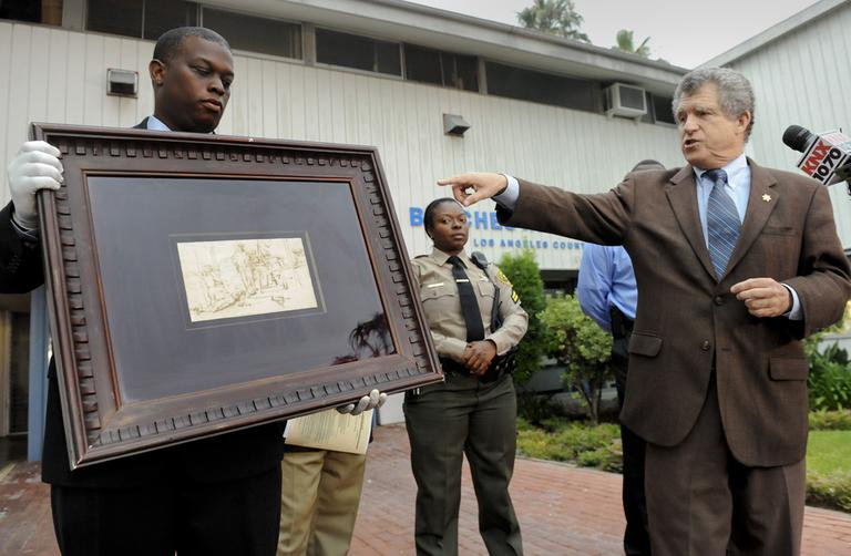 "Los Angeles Sheriff detective Clarence Williams, left, and spokesman Steve Whitmore display the recovered $250,000 Rembrandt drawing known as ""The Judgment"", Tuesday in Marina Del Rey, Calif. (AP)"