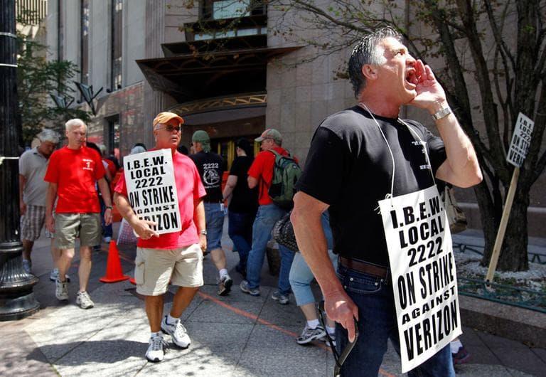 Verizon worker Steven Simard, right, of Danvers, pickets outside a Verizon office in Boston on Aug. 12. (AP)