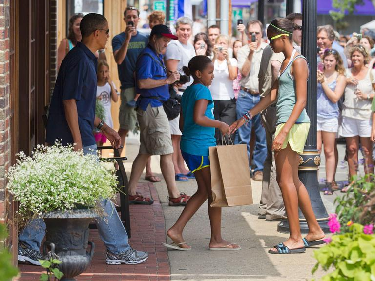 President Obama, with daughters Malia, right, and Sasha, leave the Bunch of Grapes bookstore in Vineyard Haven Friday. (AP)