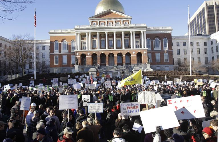"Union workers and supporters of Wisconsin workers as well as people against unions and collective bargaining attend a Massachusetts Teachers Association ""Stand Up for Wisconsin Workers"" rally outside the State House in February. (AP)"