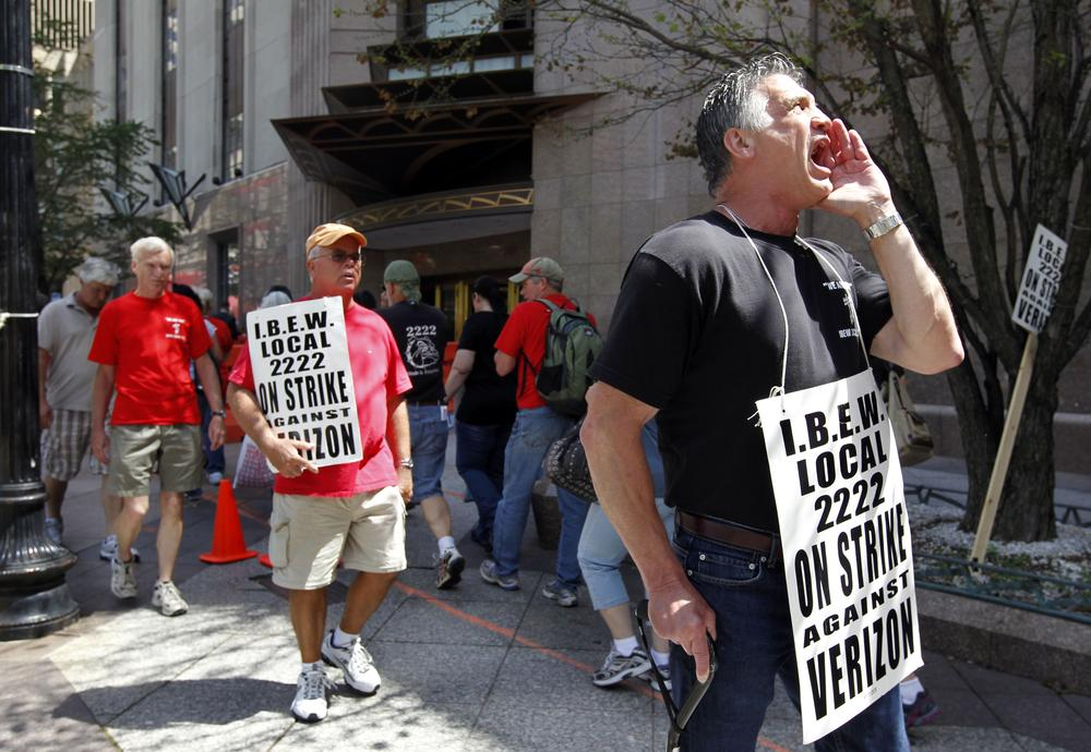 Verizon worker Steven Simard, of Danvers, right, holds a placard and chants slogans from a picket line outside a Verizon office in Boston Aug. 12. (AP)