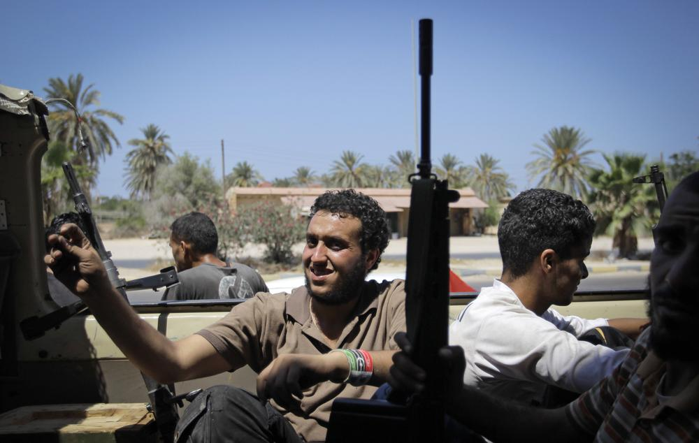 Rebel fighters drive toward the frontline in the village of Mayah, some 30 kilometers west of Tripoli, Sunday. (AP)