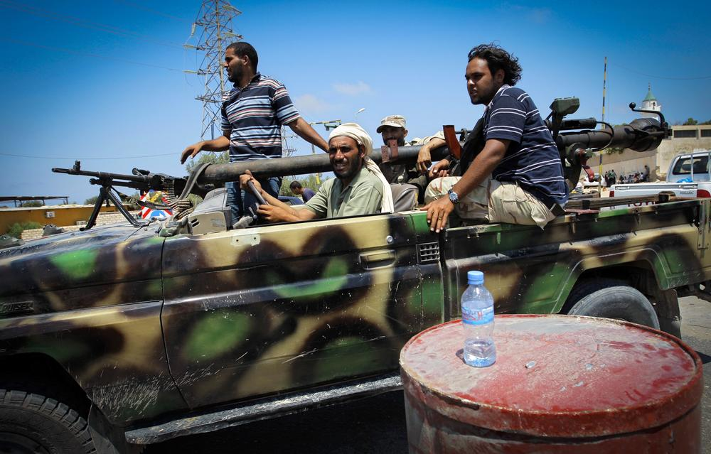 Rebel fighters speed toward frontllne fighting in the village of Mayah, west from Tripoli, Sunday. (AP)