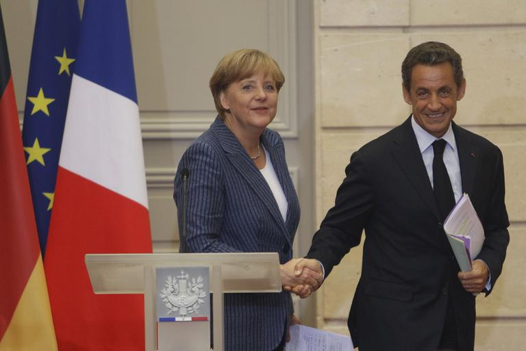 German Chancellor Angela Merkel, left, and France's President Nicolas Sarkozy, right, shake hands after their joint press conference at the Elysee Palace, Tuesday Aug. 16, 2011. (AP)