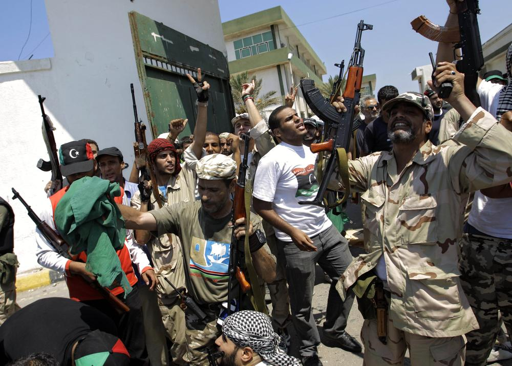 Libyan rebel fighters gesture at the former female military base in Tripoli, Libya. (AP)