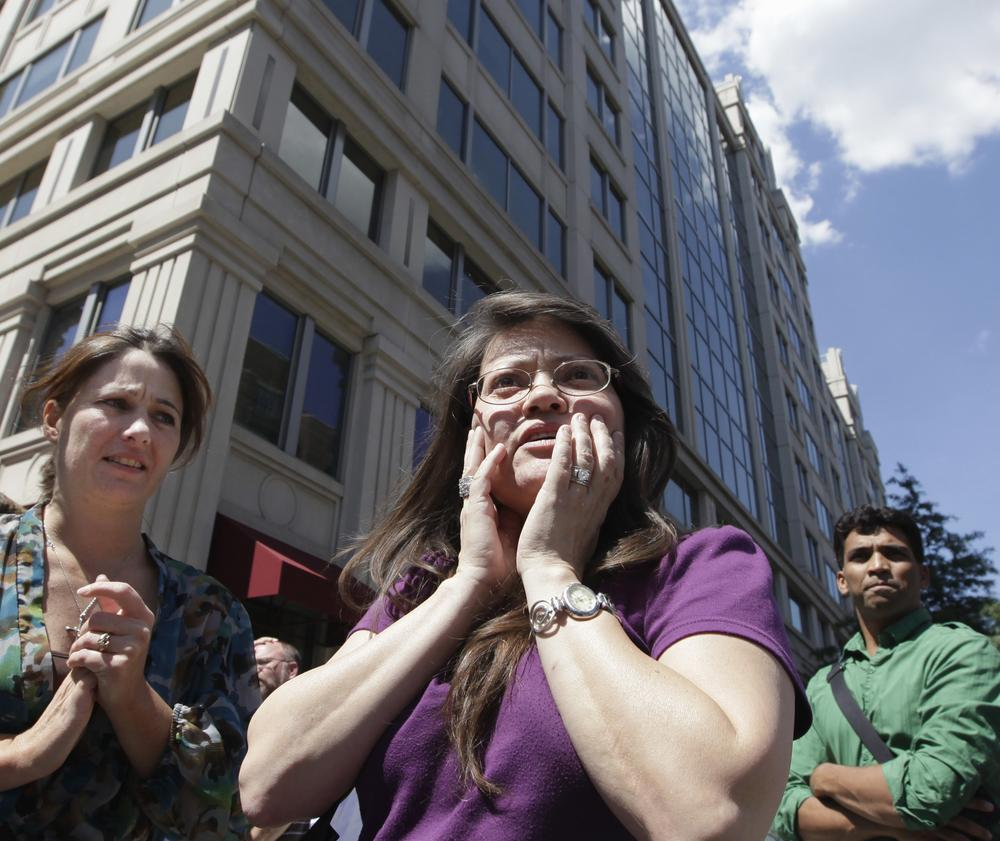 Susy Ward, center, and other office workers gather on the sidewalk in downtown Washington moments after an earthquake shook the nation's capitol. (AP)