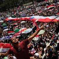 """A protester waves an Egyptian flag that reads """"We Love Egypt"""" during a demonstration after Friday prayers in Tahrir Square  in Cairo, Egypt, Friday July 29, 2011. (AP)"""