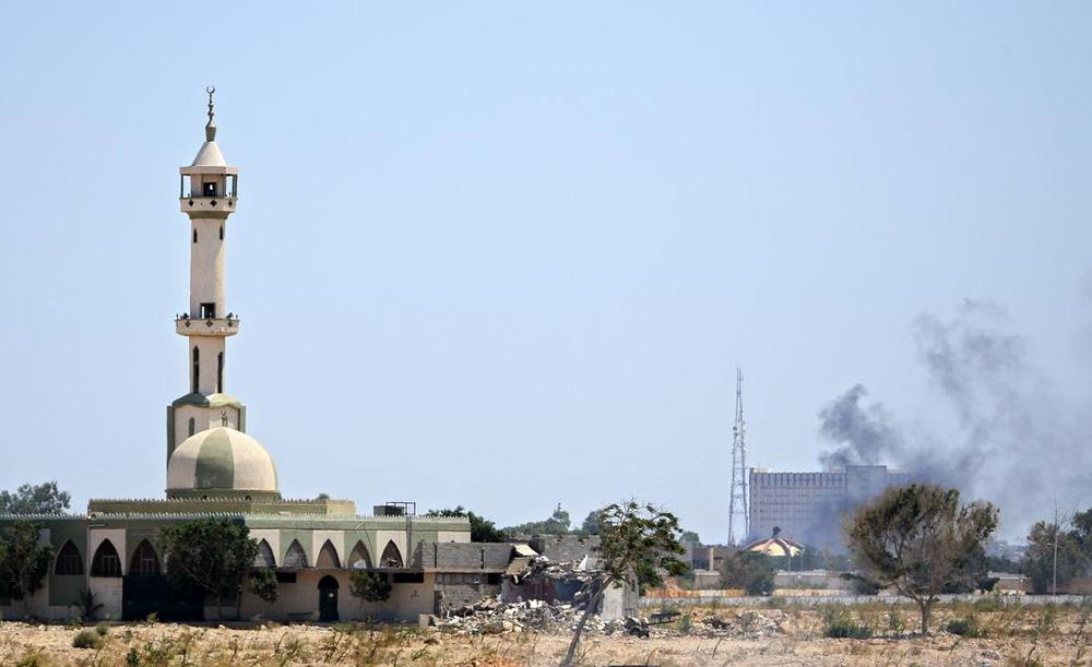 Smoke rises over buildings in the main compound of Moammar Gadhafi in the Bab Al-Aziziya district in Tripoli on Tuesday. (AP)