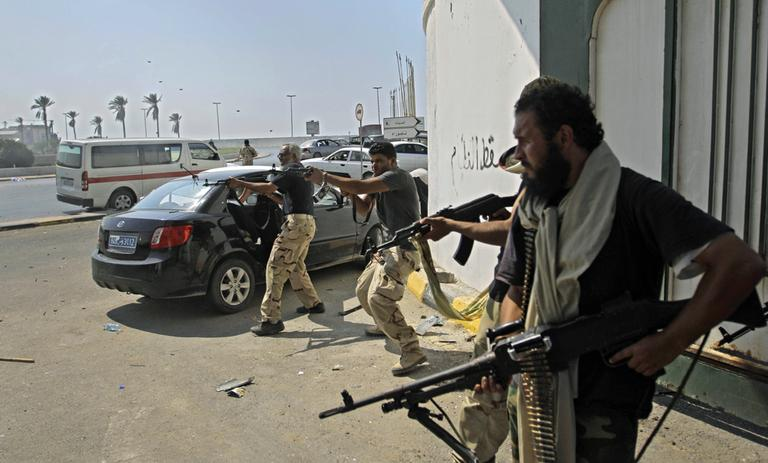 Libyan rebel fighters fire towards forces loyal to Moammar Gadhafi during fierce gunfire in downtown Tripoli, Libya, Monday, Aug. 22, 2011. (AP)