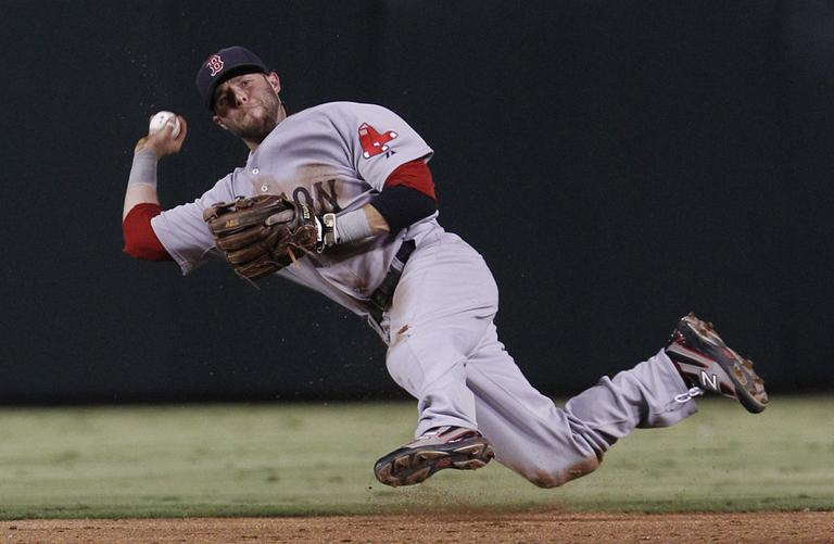 Sox second baseman Dustin Pedroia throws to first base during a game with the Rangers Monday. (AP)
