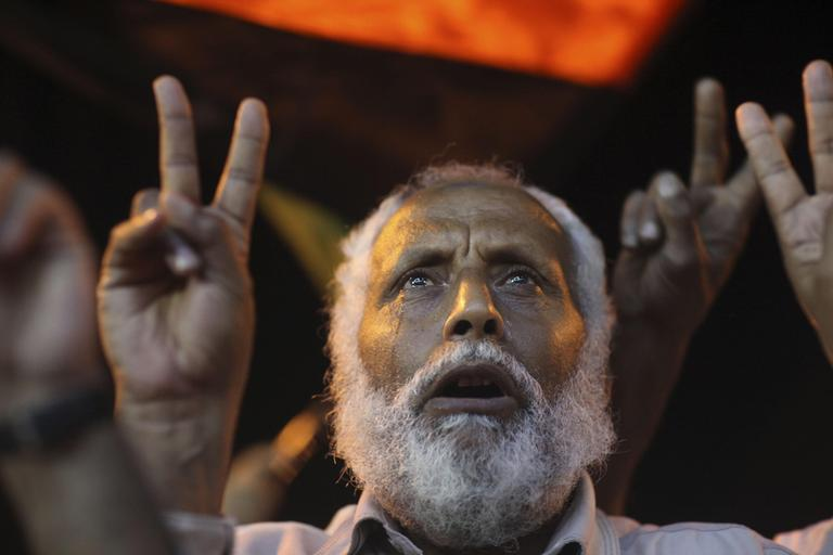 Salem Hasam Ali, 62, a shop owner, cries and flashes v-sign after singing Libya's pre-Gadhafi national anthem in the rebel-held town of Benghazi, Libya, late Tuesday. (AP)