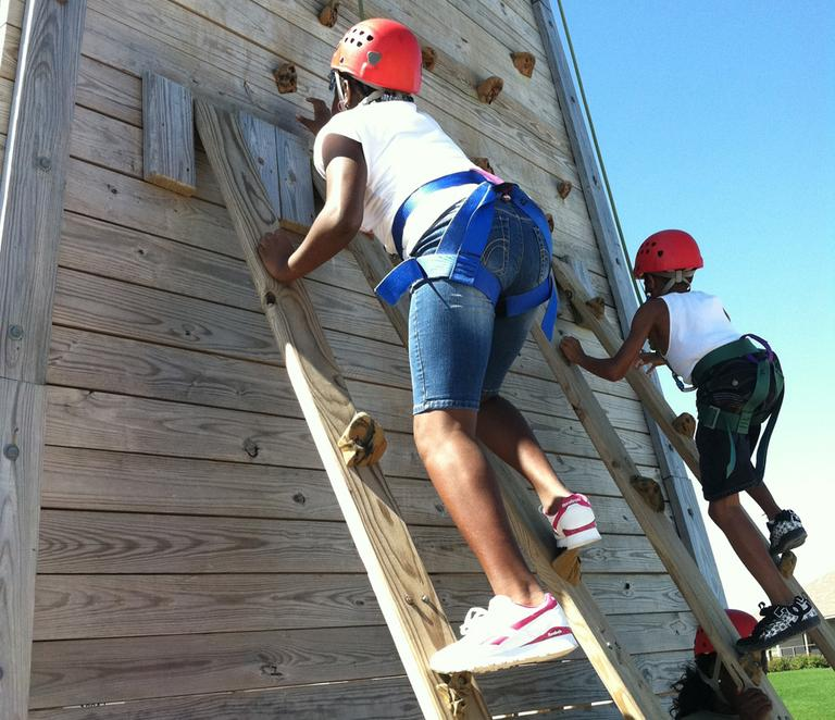 Children climbing the wall at Camp Harbor View (Delores Handy/WBUR)
