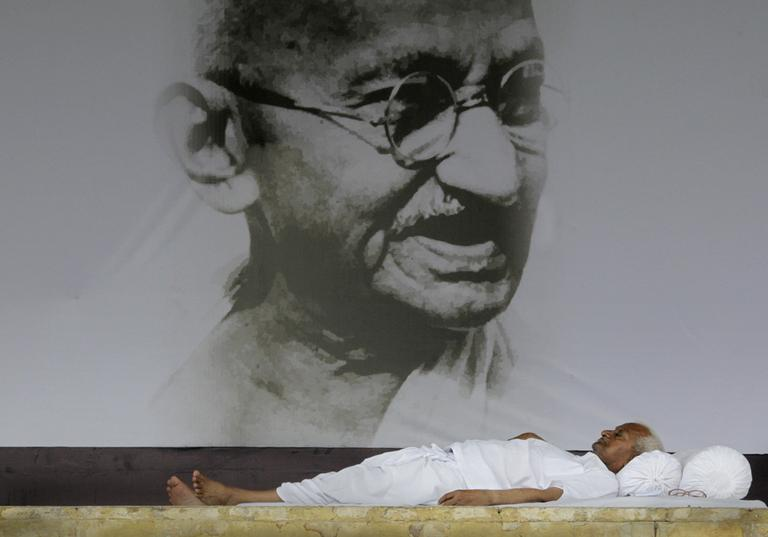 India's anti-corruption activist Anna Hazare rests in front of a giant portrait of Mahatma Gandhi on the ninth  day of his hunger strike, in  New Delhi, India, Wednesday, Aug. 24, 2011.  (AP)