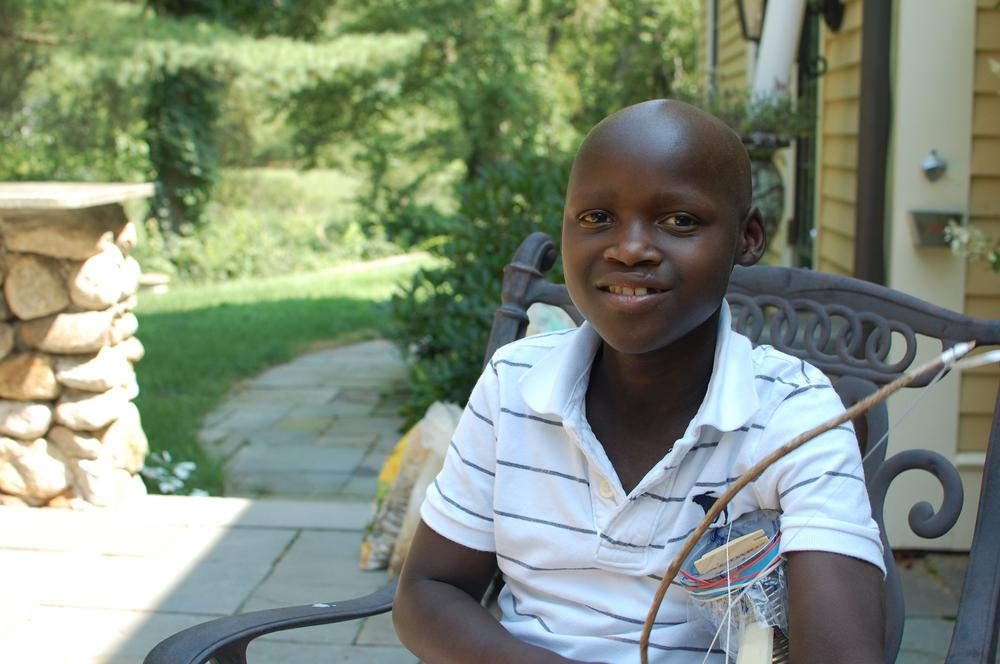 Sibo Tuyishimire, age 13, plays a violin he made during his stay in the U.S. for a bone marrow transplant. He's scheduled to return home to Rwanda later this year. (Jill Ryan/Here & Now)