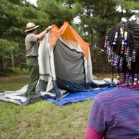 A ranger sets up a tent for a visitor at Floyd Bennett Field. (Courtesy of Gateway National Recreation Area)