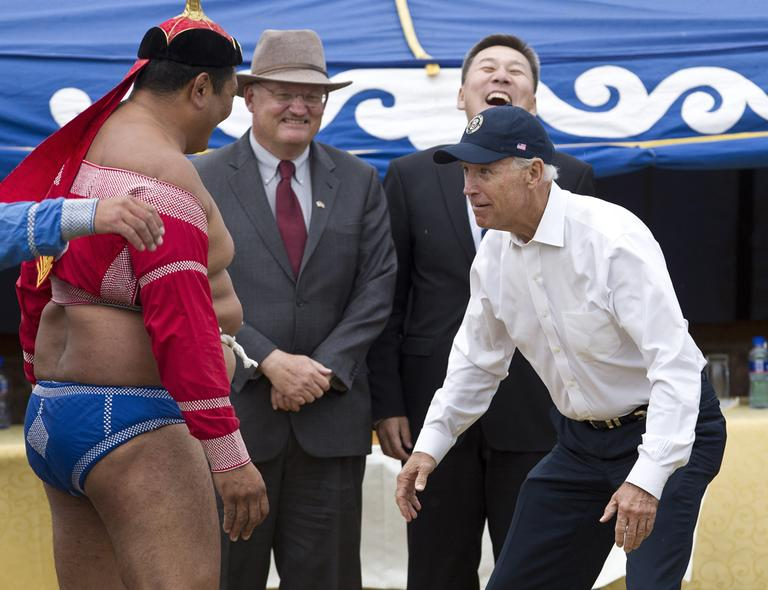 U.S. Vice President Joe Biden, right, meets Mongolian wrestler during Mini Nadam, or Mongolian wrestling performance, in Ulan Bator, Mongolia, Monday, Aug. 22, 2011. (AP Photo/Andy Wong)