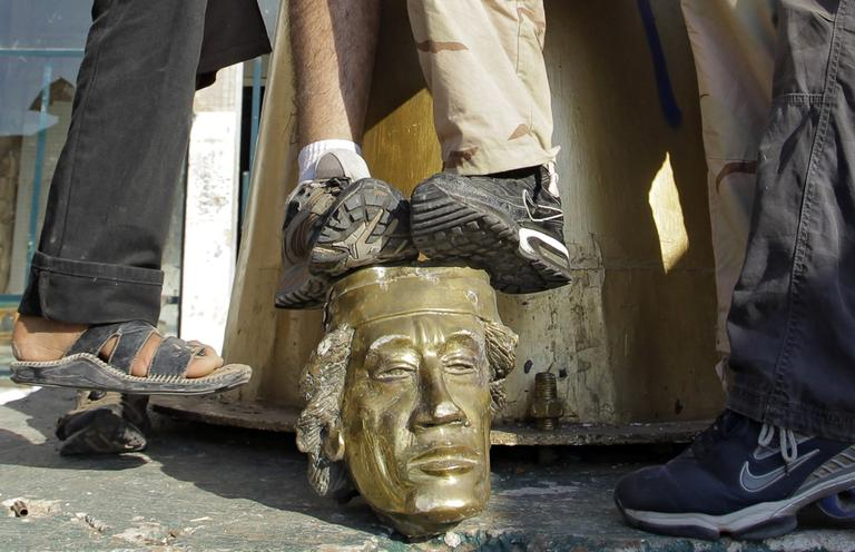 Rebel fighters trample on a head of Moammar Gadhafi inside the main compound in Bab al-Aziziya in Tripoli, LIbya, Tuesday, Aug. 23, 2011.  (AP)