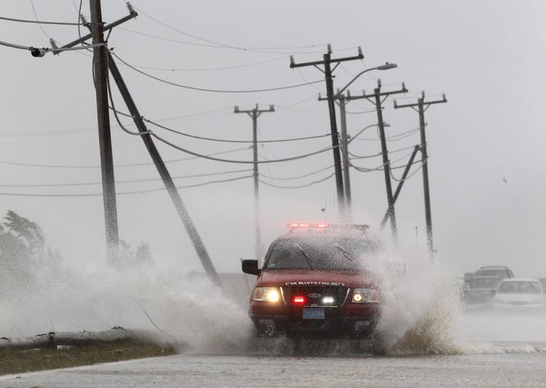 An Oak Bluffs Fire Department vehicle is buffeted by strong winds and ocean spray from Tropical Storm Irene while driving along a costal road in Edgartown Sunday. (AP)