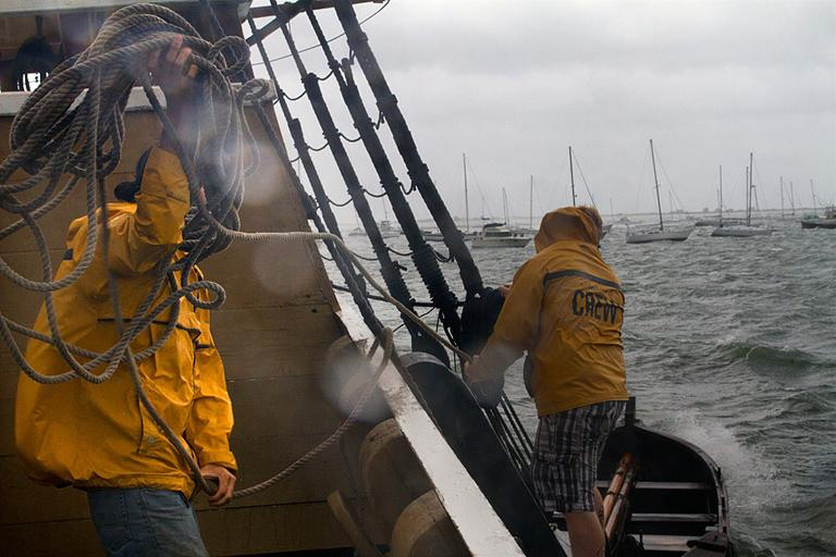 Crewmembers of the Mayflower II in Plymouth struggle to wrangle a loose utility boat. (Jesse Costa/WBUR)