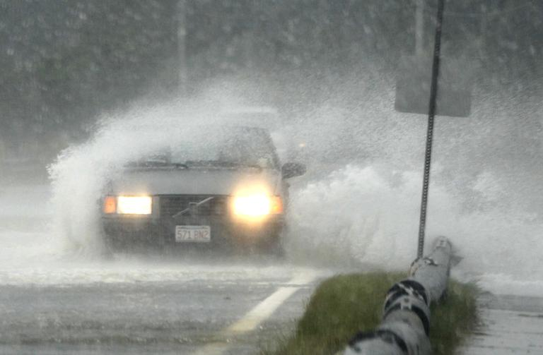 A passenger vehicle is buffeted by strong winds and ocean spray from tropical storm Irene while driving along a coastal road in Oak Bluffs, Sunday. (AP)